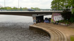 Obdachlose unter Kennedybrücke mit kleinem Garten rechts